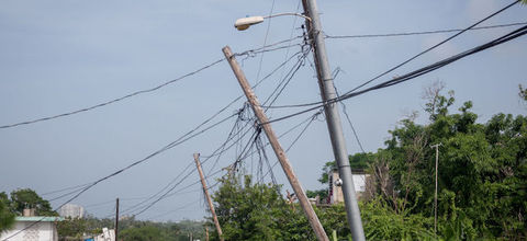 Damaged electrical poles against a blue sky in Luquillo, Puerto Rico