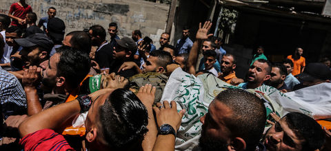 A crowd of brown men carries the brown body of Marwan Nasser through the streets.