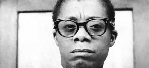 James Baldwin. Black and white archive photo of Black man, dark short hair, wearing black glasses and white shirt with a dark tie.