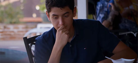 """""""Living Undocumented."""" Young Latinx man with short dark hair wearing blue polo shirt."""