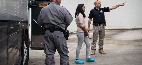 A person with dark hair wearing a pink sweater and gray leggings is handcuffed, flanked by two people.
