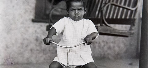 Richard Samuel Roberts photograph. Black and white photo of Black toddler in a white dress and white socks, sitting on a tricycle.