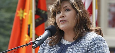 Kimberly Teehee. Indigenous woman wearing blue and white jacket speaking at a podium with brightly colored flags behind her