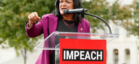 Pramila Jayapal. South Asian American woman wears a pink blazer as she speaks before a crowd and stands behind a podium that has a red and white sign attached that reads: IMPEACH.