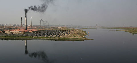 industrial plant releases pollutants into the air next to a waterway