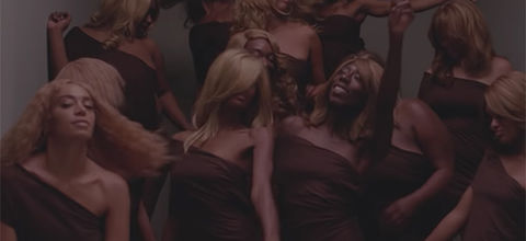 """""""When I Get Home"""" video. Several Black women wearing blonde wigs and matching brown outfits."""