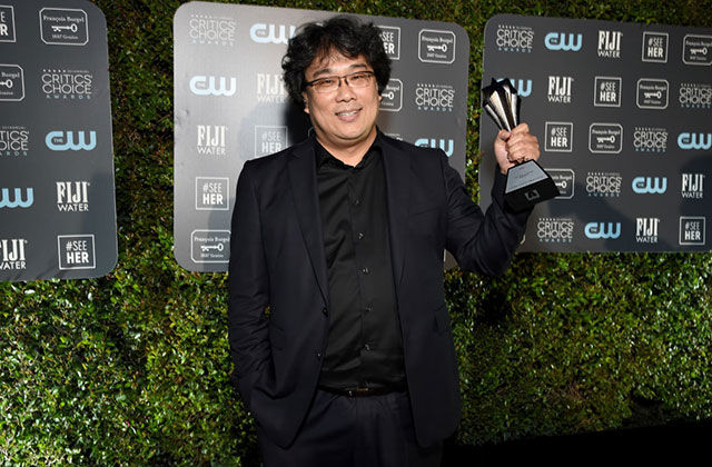 Bong Joon Ho. Korean man with dark hair wearing black jacket and shirt holding a Critics' Choice Award.