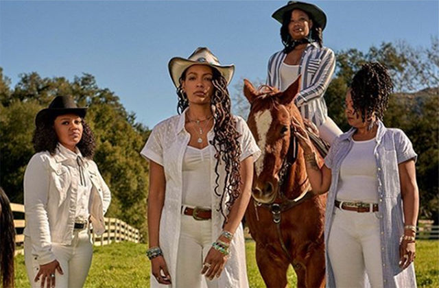 Cowgirls of Color. Four Black women dressed in white tops and white jeans wearing cowboy hats. One is sitting on a brown horse.
