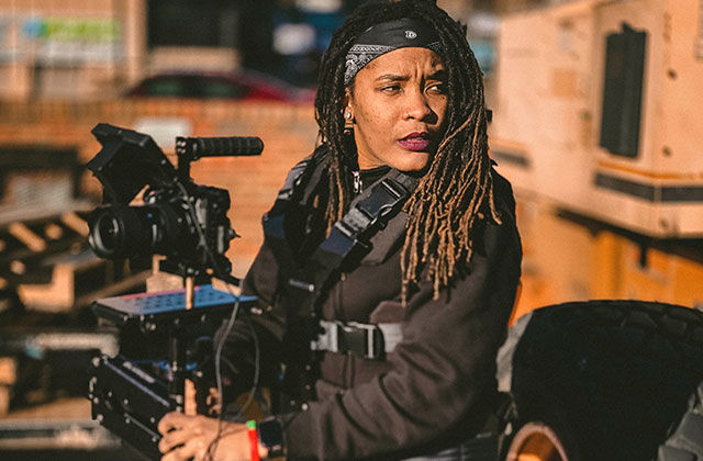 Firelight. Black person with long brown locs wearing black clothing with a black headband, holding  a large camera.