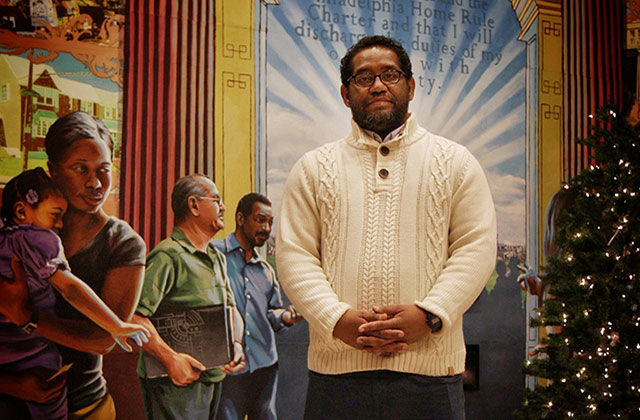 James Hough. Black man with short dark hair and beard wearing cream colored sweater, jeans, standing in front of a mural.