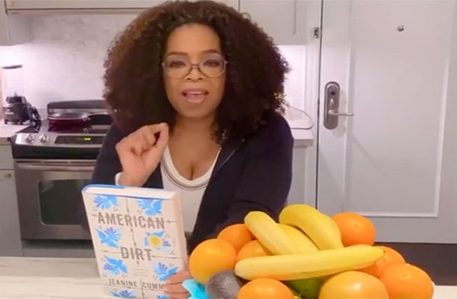 "Oprah Winfrey. Black woman with shoulder length curly brown hair wearing cream top and black cardigan, standing at a kitchen counter in front of a fruit bowl, while holding the book ""American Dirt."""