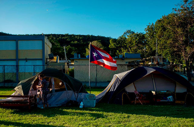 Person stands in front of two tents on a field with the Puerto Rican flag flying in between.