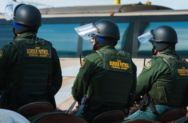 three US Border Patrol agents in green uniforms stand side by side with their backs to the camera.
