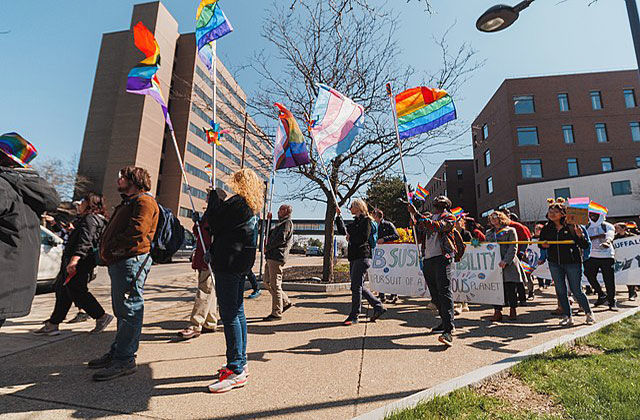 People walking carrying transgender and LGBTQ flags.