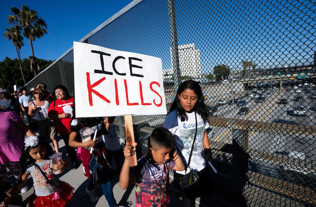 "Young boy holds protest sign that reads, ""ICE Kills"""