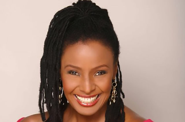 B. Smith. Black woman with long dark locs pulled into high ponytail, wearing off-the-shoulder top.