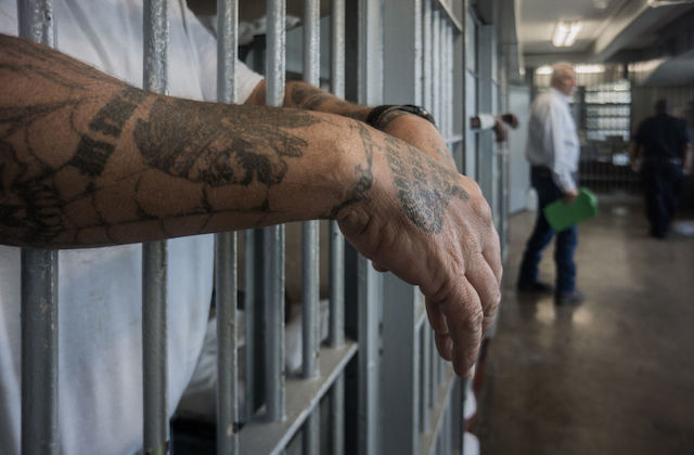 Man with tattoos on his hands and forearms hangs his hands through jail cell bars.