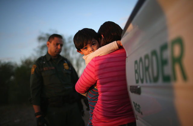A small, dark-haired boy hugs his mother tightly as she holds him and wraps him in her arms. She stands near a truck marked BORDER.