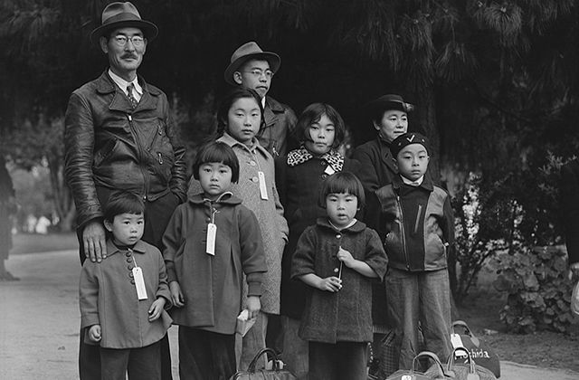 Japanese American family. A large family, including seven children in various ages, huddled wearing name tags.
