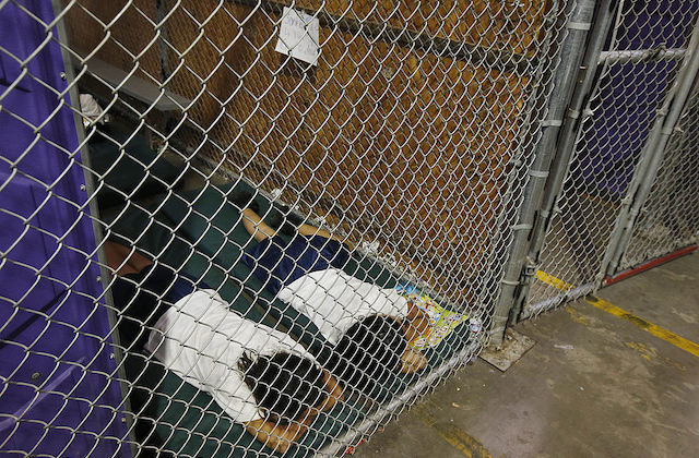Two people wearing white t-shirts lie face down on a black mat inside of a wire cage inside an Arizona immigration detention center.