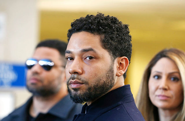 Jussie Smollett. Black man with short mustache and beard and short dark curly hair wearing dark suit jacket.