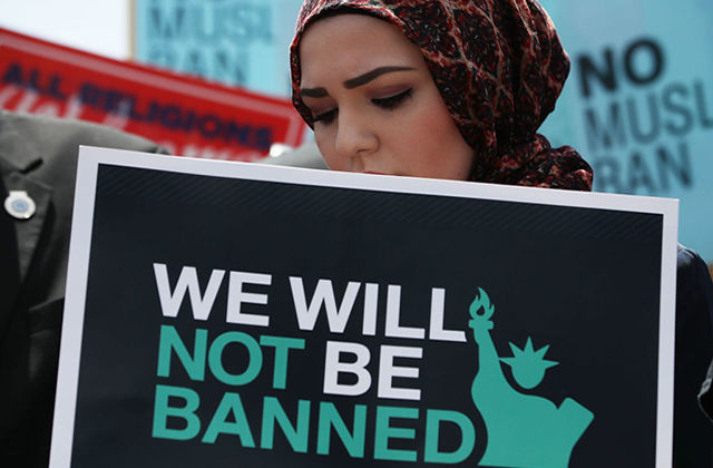 "Muslim Ban. Muslim woman wearing brown headscarf and carrying a sign reading ""We will not be banned"""