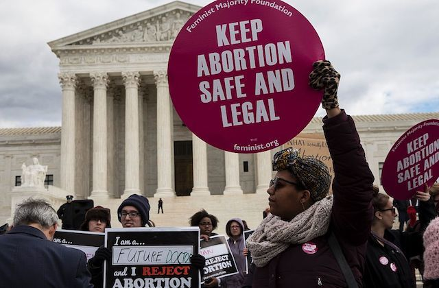 "A group of protestors, one holding a sign that reads ""Keep Abortion Safe and Legal"" stand in front of the Supreme Court of the United States."