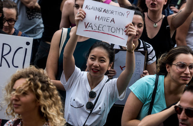 "An Asian woman in a white t-shirt is at a protest and holds a sign that reads ""Against abortion? Have a vasectomy."""