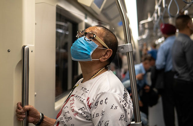 COVID-19. Asian American wearing blue medical mask and white T-shirt stands on train holding pole.
