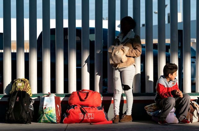 A parent and child hold all their belongings and lean against a large, white fence.