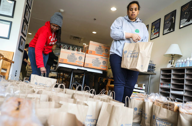 Two organizers are packing food packages for those affected by the Coronavirus pandemic.