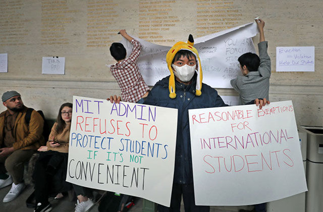 Coronavirus protest. Asian-American student wearing yellow hat, white face mask, blue coat holding up to two protest signs.