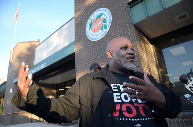 "Black man wears a t-shirt that reads, ""let my people vote"" as he stands in front of a brick building."