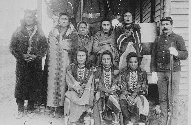 Native Americans. Archival black and white image showing seven Native Americans on a porch, next to a White man wearing an army uniform.