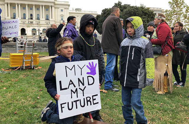 "Native American Land Protest. Three young boys stand around a sign reading ""My land my future."""