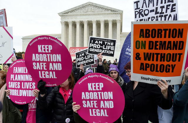 Protesters hold both pro-choice and anti-abortion signs in front of the U.S. Supreme Court.