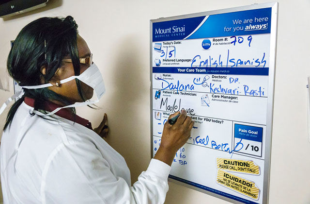 Black nurse. Black woman with dark hair wearing a white mask and lab coat writing at a schedule board.