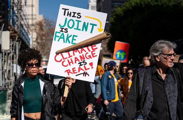 "Earth Day. Black woman marching in strike holding a sign with a giant spliff that reads: ""This joint is fake, climate change is real."""