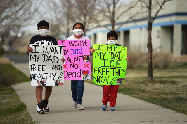 "three Latinx children a boy, 10, a girl, 11, a boy six, hold signs in front of them like ""I don't want my dad free and healthy"""