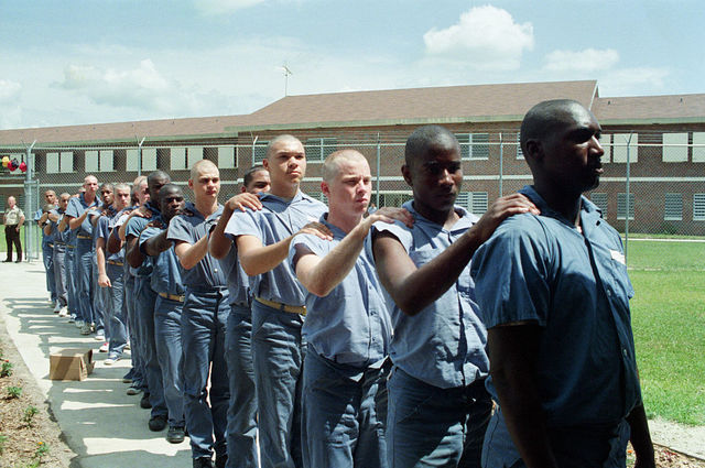Single file line of bald headed men, black and white in blue prison uniforms lined up with one hand on the person's shoulder in front of them.