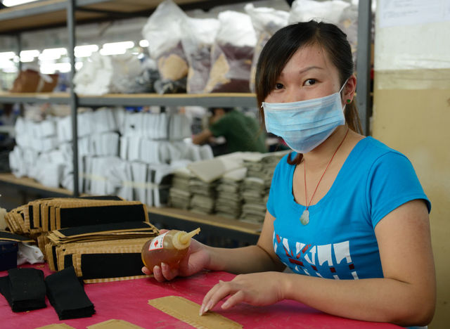 Young Chinese woman seated in a factory with a blue t-shirt, blue face mask, glue in one hand, and fabric on a table.