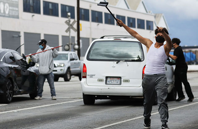 Los Angeles COVD-19. Three men wearing face masks on a highway using squeegees to clean car windows.