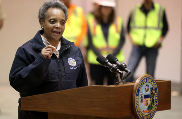 Chicago Mayor Lori Lightfoot. Brown-skinned Black woman with short salt and pepper hair, dressed in a blue windbreaker jacket