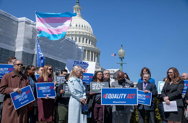 Trans health. A cluster of people in winter coats standing around a podium holding blue signs with the trans flag waving in the background in front of the U.S. Capitol.