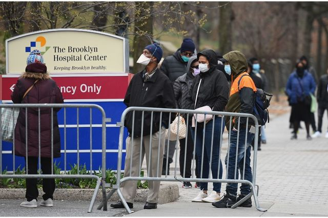 Mostly African Americans stand in line behind a metal barricade with masks on outside of The Brooklyn Medical Center