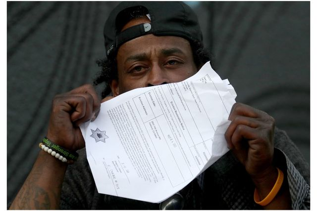 Black man with backwards cap, 30s, holding eviction papers in front of his face. Only his eyes are showing.