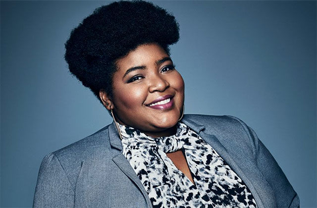Dulcé Sloan. Black woman with dark afro wearing blue suit jacket and floral blouse.
