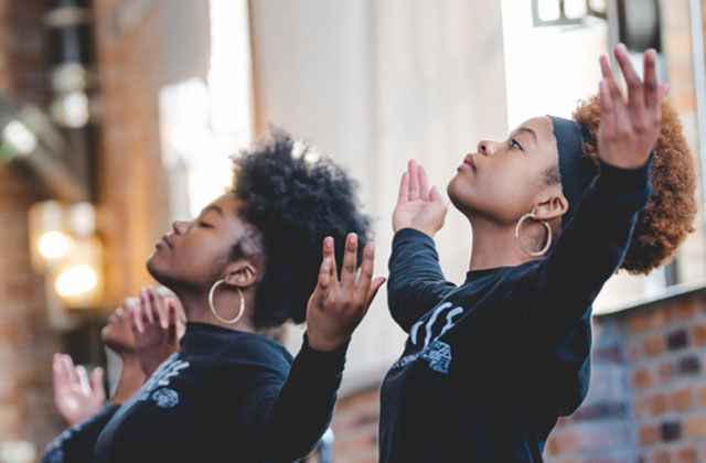 Love is Healing Fund. Two young Black women with Afros wearing black tops with both arms raised.