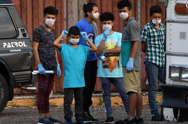 four young Honduran boys stand next to each other and wear white face masks.