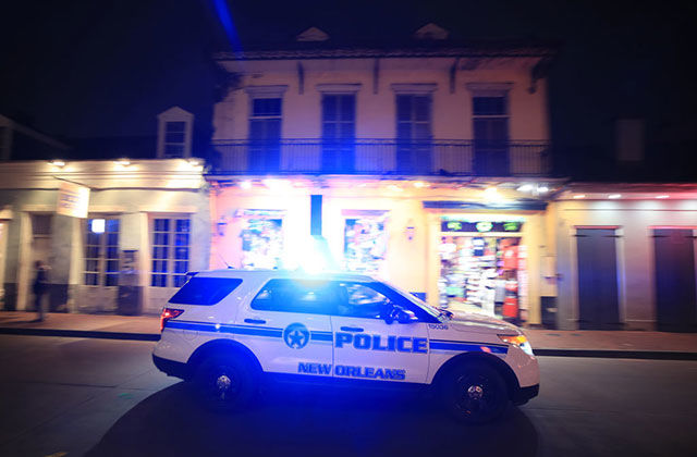 NOPD. White police cruiser with blue letters reading Police New Orleans, driving down a street with lights on.